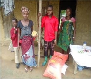 Four member of a family stand outside their home in Sierra Leone with a sack of rice and other food supplies they have just received.