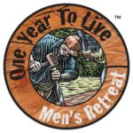 "Circular logo; outer ring is a wood-colored background with the text ""One Year To Live"" in black and ""Men's Retreat"" in white; inner circle has a drawing of white man in a denim shirt and orange baseball cap working with a chisel and hammer. He is outdoors."