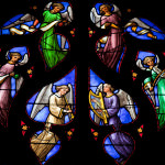[Image description: Stained glass window with images of angels.]