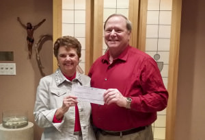 Virginia Worley presents Bishop Kevin Kanouse with a check from the Lutheran Foundation of the Southwest to NT-NL.