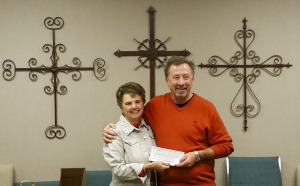 LSFW Board President Virginia Worley presents Pastor Phil Geleske with a check