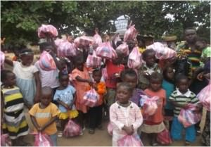 Children in the Sierra Leone community of Krissy Town hold up their bags of take-away food, after one of the wet feeding programs.
