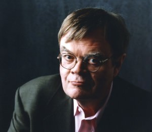 Garrison Keillor [Image description: headshot of Garrison Keillor, a white man with brown hair and glasses, wearing a pastel-colored button-down shirt and a black blazer, looking at the camera,]