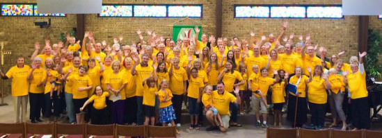 """[Image description: a large group of members of Christ the Servant Lutheran Church in Allen smile and wave at the camera in their yellow """"God's Work. Our Hands."""" Sunday t-shirts.]"""