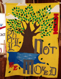 "[Image description: Photo of a church banner showing a tree with a brown trunk and green leaves, planted near water; the banner background is yellow, and the words ""I shall not be moved"" are written around hte image in red and gray text.]"