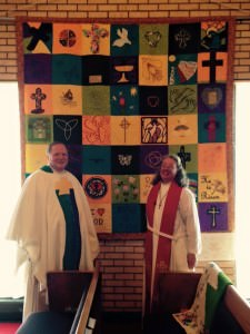 [Image description: Bishop Kevin Kanouse and Pastor Bonita Knox, wearing pastor's robes, stand in front of a colorful handmade quilt, made of squares in shades of yellow and green, with various images on them.]