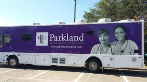 [Image description: photo of a Parkland Hospital mobile health center bus. The bus is decorated with a deep purple background and two female doctors or nurses are picture on the right side of the bus in black and white. The Parkland logo and name appear next to the women's faces. The bus is parked in a parking lot on a sunny day.]