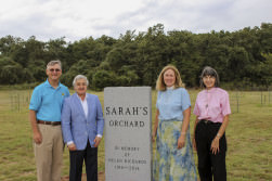 [Image description: two white men stand to the right of a large stone marker and two white women stand to the right of it. They are facing the camera and smiling. The marker reads: Sarah's Orchard, in memory of Helen Richards, 1916-2014.]