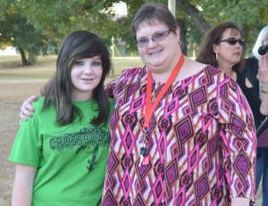 [Image description: Two white women, one a teen with long brown hair and wearing a green Crossroads t-shirt, the other an adult woman with short brown hair and glasses, wearing a patterned purple and pink shirt, stand outdoors, facing the camera and smiling. The older woman has her arm around the teen.]
