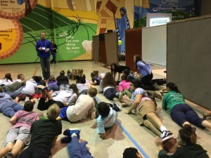 [Image description: A large group of junior high youth participate in an activity. They are lying on the floor of a large room with a colorful mosaic painted on the back wall. There is one adult leader standing, directing the youth in the activity.]