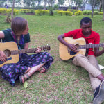 [Image description: A young white woman sits cross-legged on the grass, leaning over her guitar. To her left is a young Black man sitting on the grass with his legs out in front of him, his ankles crossed. He is also playing a guitar.]