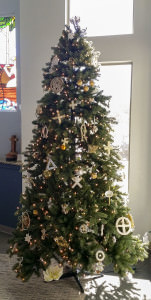 [Image description: a tall Christmas tree decorated with white and gold Chrismon ornaments]