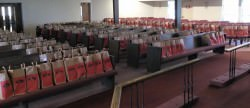 [Image description: paper grocery sacks with Thanksgiving groceries for families filling the seats in the sanctuary.]