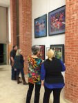 [Image description: four people, two women closer to the camera and a man and a woman further down, look at four framed works of art by Chinese artist He Qi, at the exhibit at Trinity Lutheran Church in Fort Worth.]