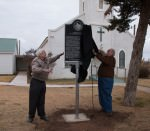 [Image description: two men unveil a historical marker in front of a church.]