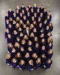 [Image description: photo of the members of St. Olaf College's Choir, dressed in their robes and looking at the camera, which is suspended above them.]