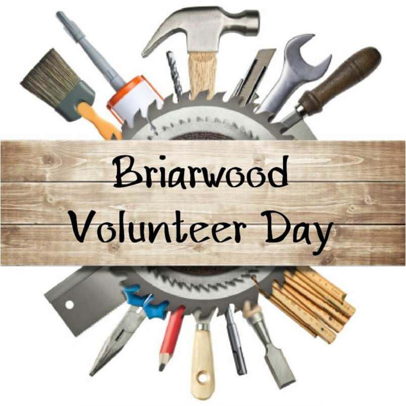 """An unfinished plank for wood with the words """"Briarwood Volunteer Day"""" in the foreground; behind the plank is a circular saw and a round array of construction tools."""