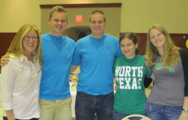 [Image description: five white college-age people stand side-by-side, arms around each other's shoulders. They are smiling at the camera. One woman is wearing a green University of North Texas t-shirt.]